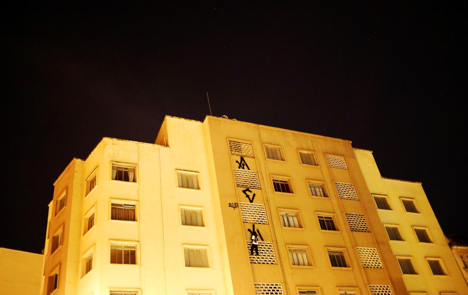 """En """"pichador"""", altså en som driver med graffiti, signerer en ni etasjer høy bygning i Sao Paulo i Brasil."""