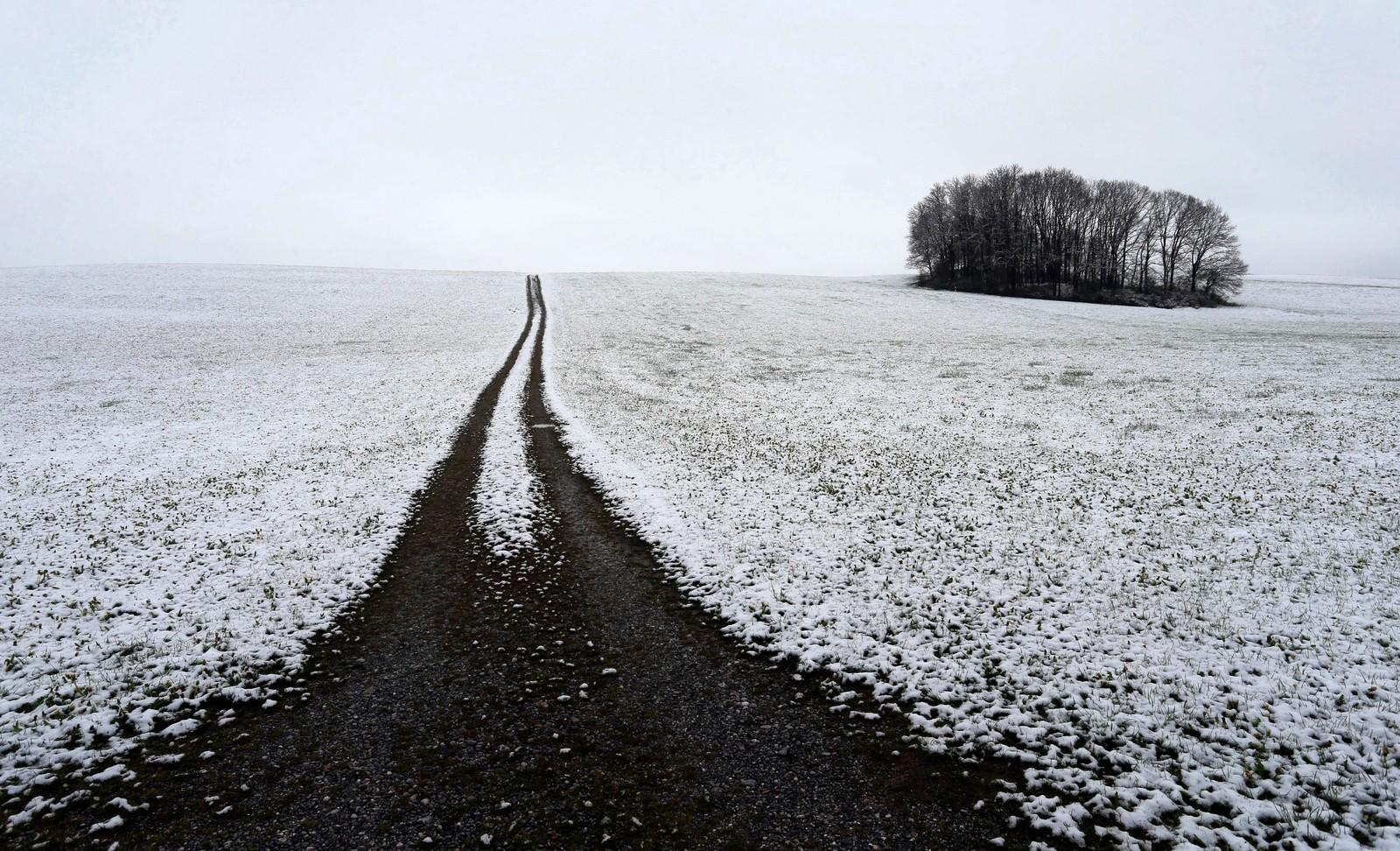 En landevei kutter det snøkledde landskapet i to nær Apfeltrang i Tyskland.