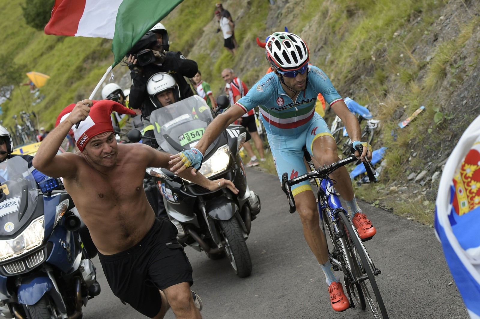 Også de andre rytterne måtte hanskes med tilskuere. Her må Vincenzo Nibali dytte vekk en nærgående supporter. AFP PHOTO / LIONEL BONAVENTURE