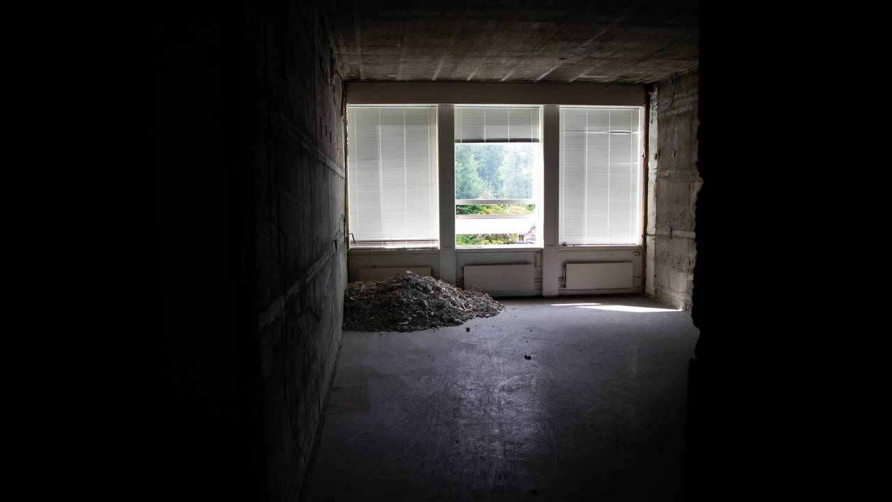 Man ser et tomt, mørkt rom med vinduer i enden, dekket med persienner. På gulvet ligger det en haug med murstein i hjørnet.