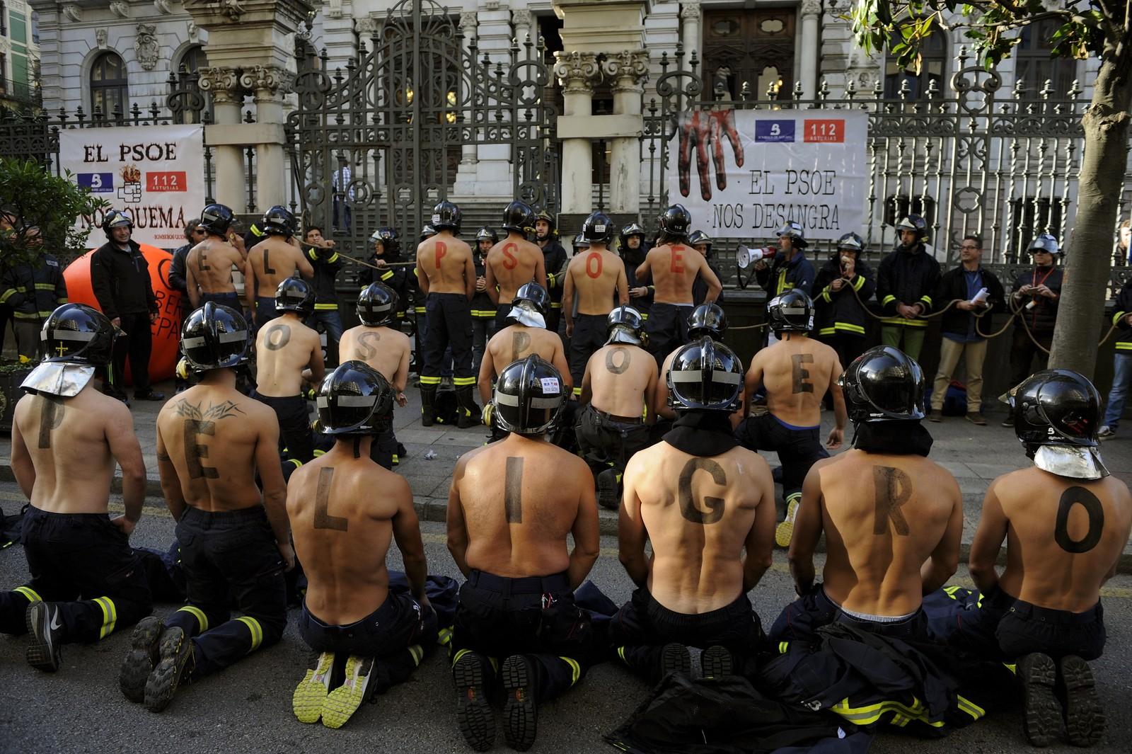 Spanske brannmenn demonstrerte på denne måten i Oviedo, Spania, denne uka. De krever bedre lønninger og sikkerhet. Bokstavene malt på ryggtavlene former ordene PSOE (Spanias sosialistiske parti) setter deg i fare.