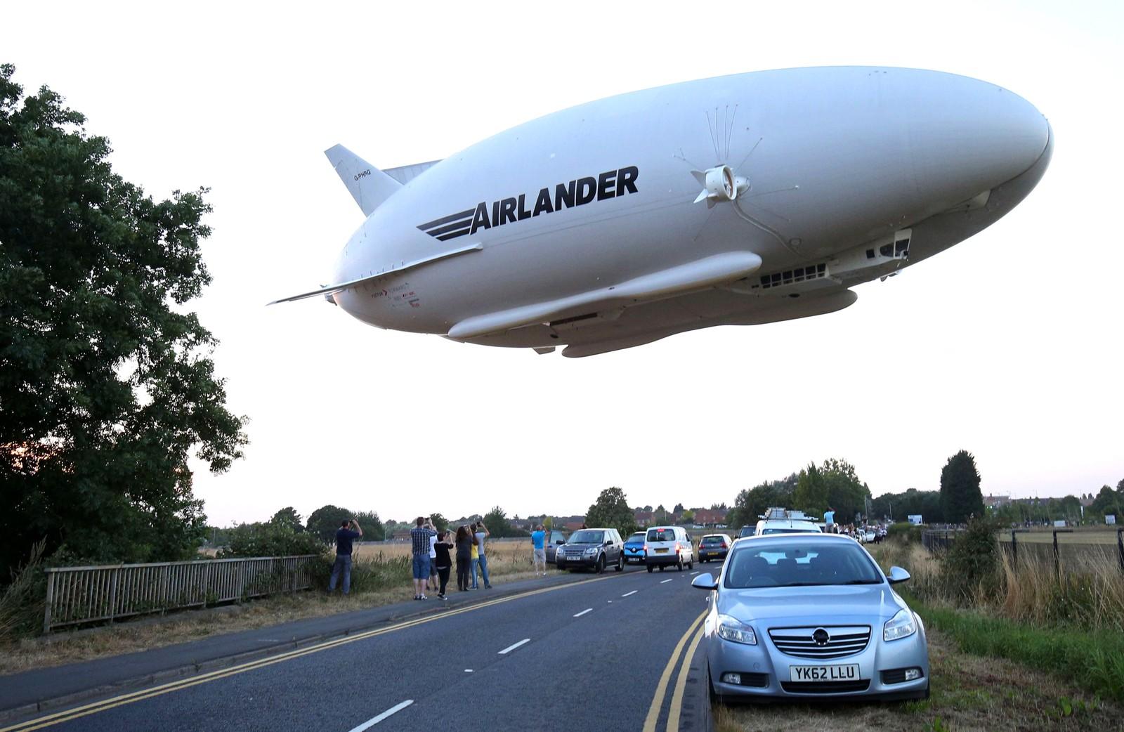 Dette er Hybrid Air Vehicles HAV 304 Airlander 10, verdens største luftfartøy, på jomfruturen nord for London i England den 17. august. Fartøyet er 92 meter langt, 43,5 meter bredt og 26 meter høyt. Det er fylt med helium og blir drevet av fire dieselmotorer. Ifølge selskapet som står bak, kan fartøyet være i luften i fem uker i strekk når det er ubemannet, og to uker hvis det er bemannet og farten er på 150 km/t. Det tåler en lastevekt på opptil 10.000 kg. Vokalisten i Iron Maiden, Bruce Dickinson, som selv er pilot, skal være en av investorene.
