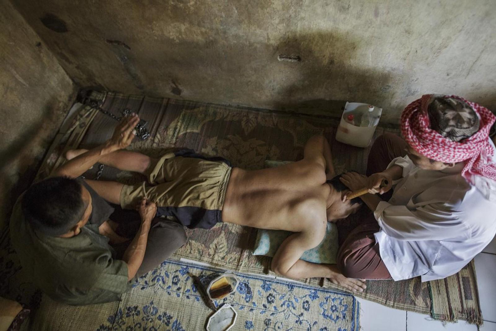 Haji Hamden, en islamsk healer, messer mens assistenten Abdul slår leggene til en innlagt i Pengobatan Alternatif Nurul Azha, et tradisjonelt healingsenter vest på øya Java.