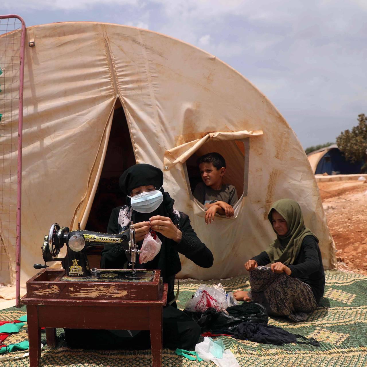 Den syriske kvinnen Umm Hussein syr munnbind i et telt i en flyktningleir i nordvest-Syria.