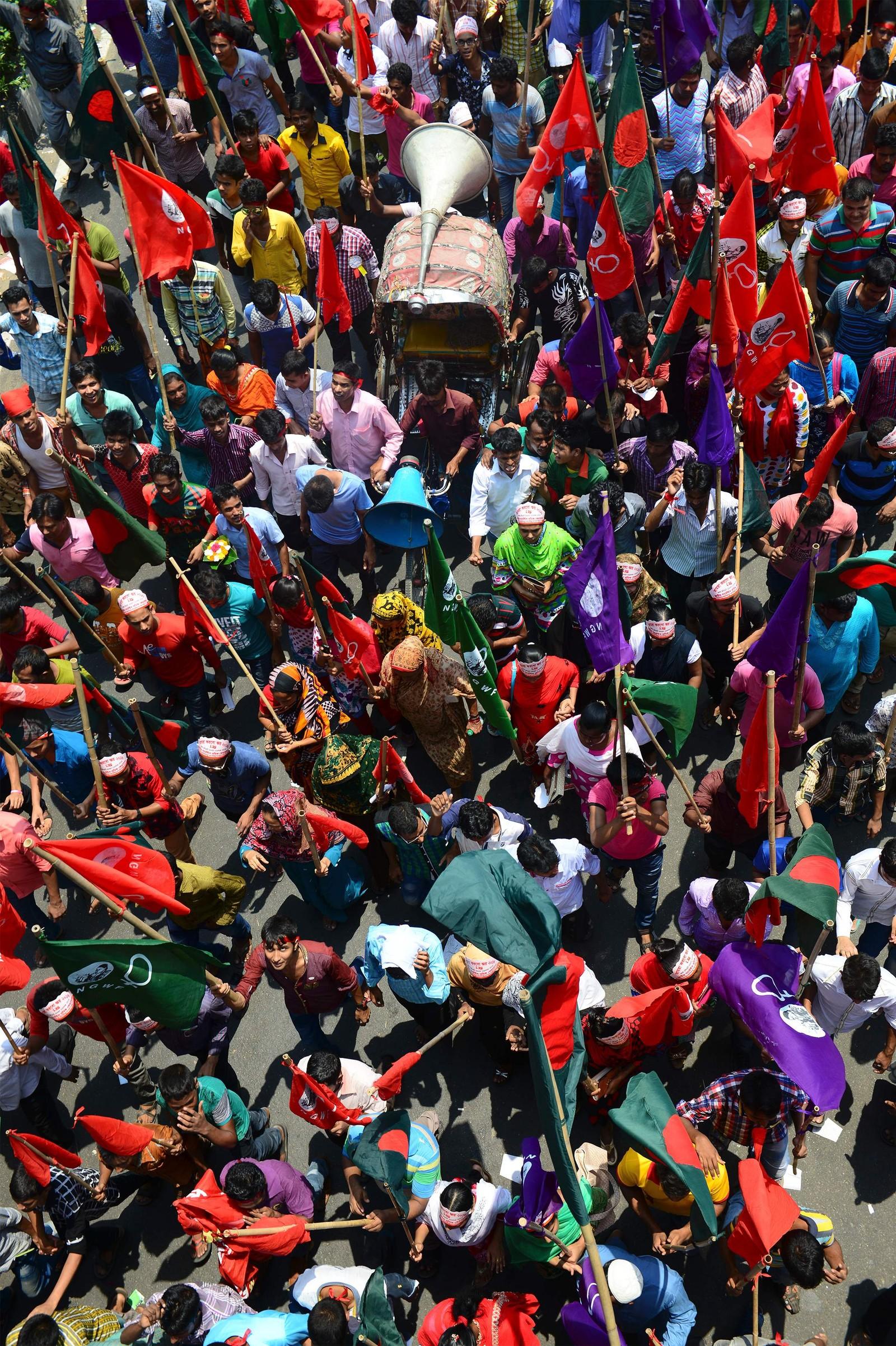 Arbeidere i Bangladesh roper slagord og vifter med flagg under en markering i Dhaka på arbeidernes dag, 1. mai.