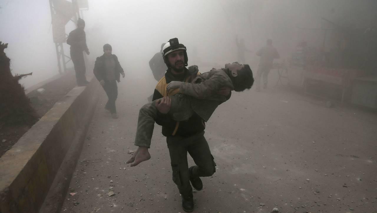 Hjelpearbeider fra De hvite hjelmene bærer bort skadet barn etter bombing i Øst-Ghouta 9.januar 2018
