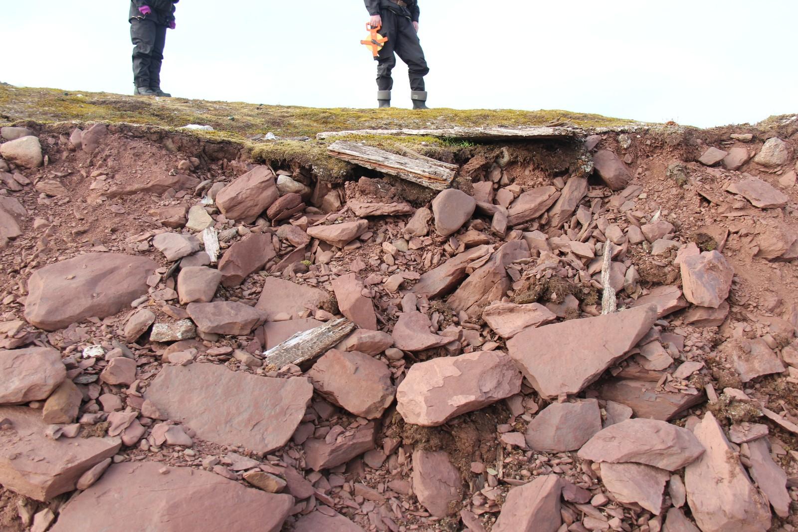 Plankerestene av ei grav faller i sjøen ved Reinsdyrflya.