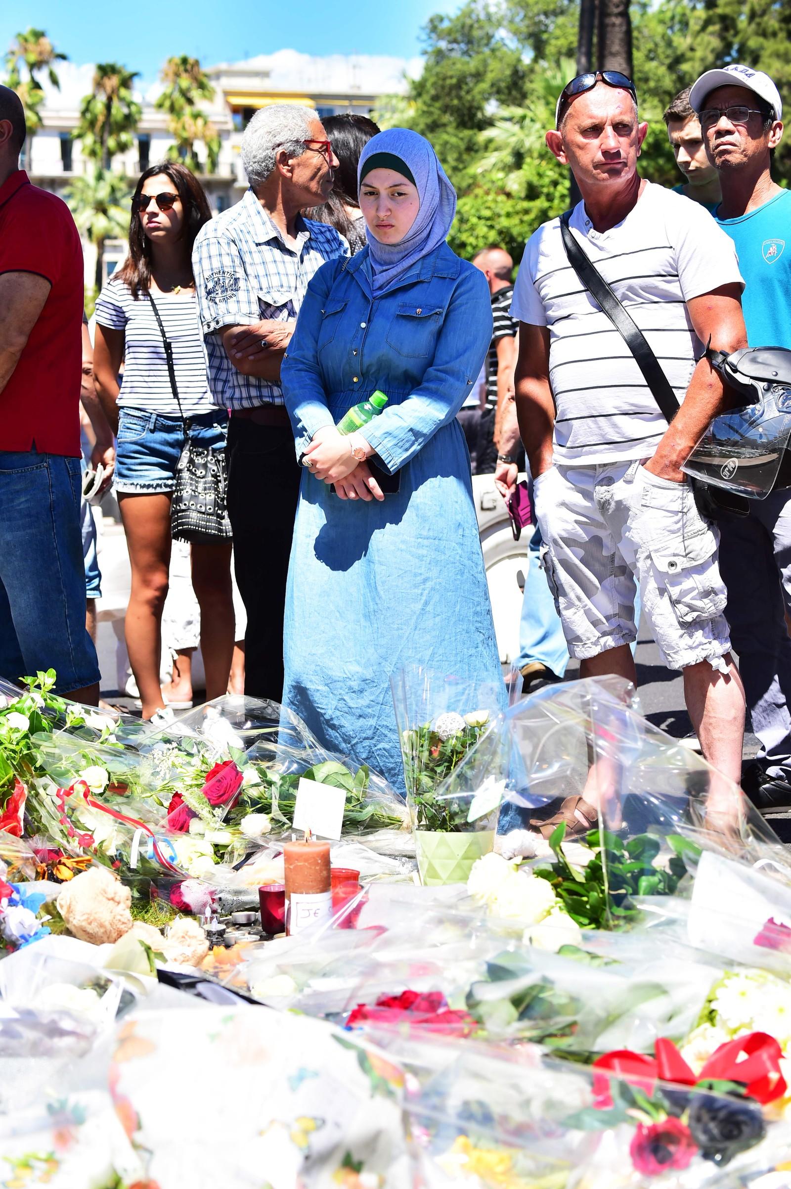 Sørgende og blomster i Nice ser på blomster til minne om ofrene for terrorangrepet i Nice 14. juli