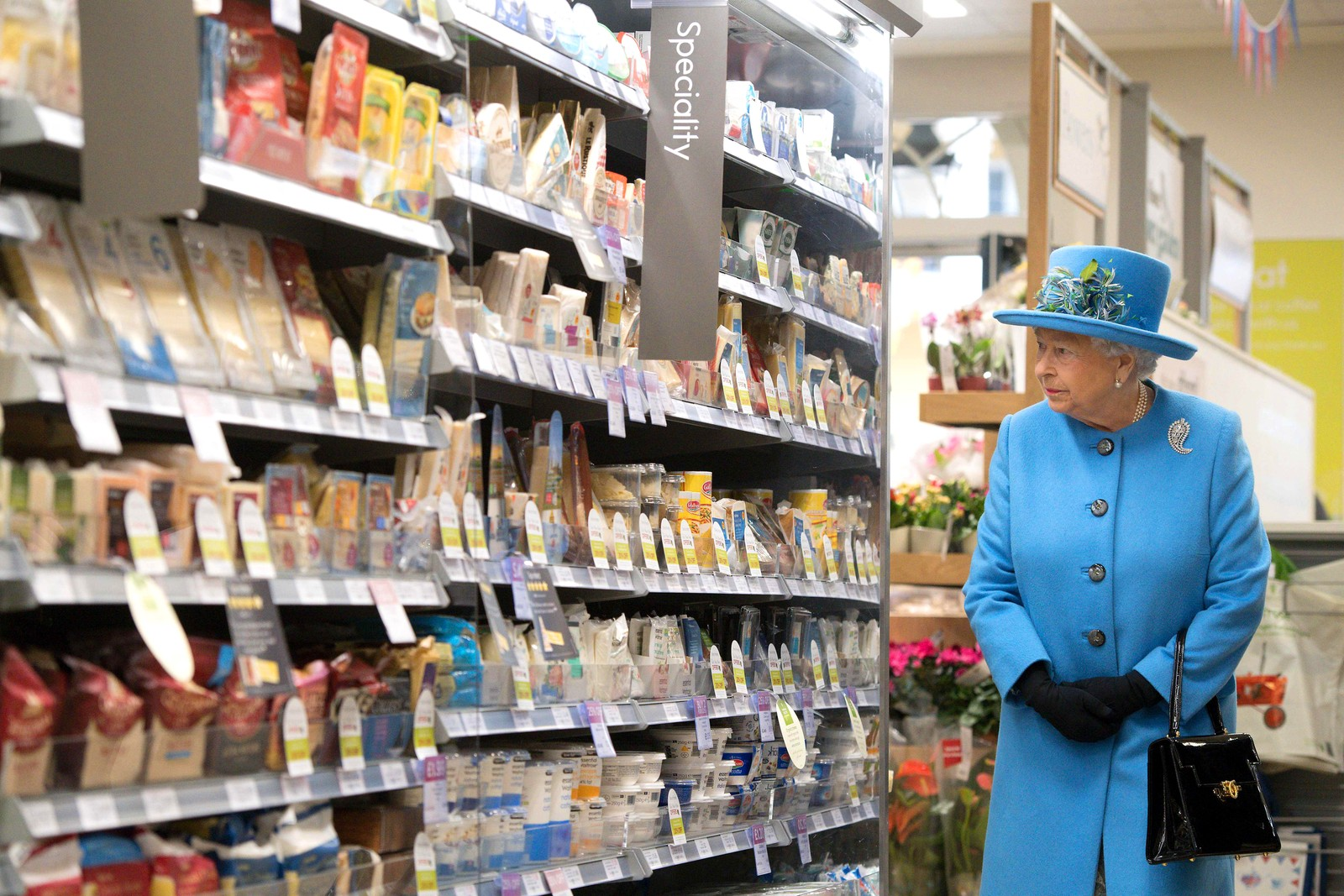 Dronning Elizabeth II er på besøk på supermarkedet Waitrose i Poundbury i England. Poundbury er en eksperimentell landsby bygget etter ideer av Prins Charles hvor man forsøker å utfordre etterkrigens tanker om hva moderne byplanlegging er.