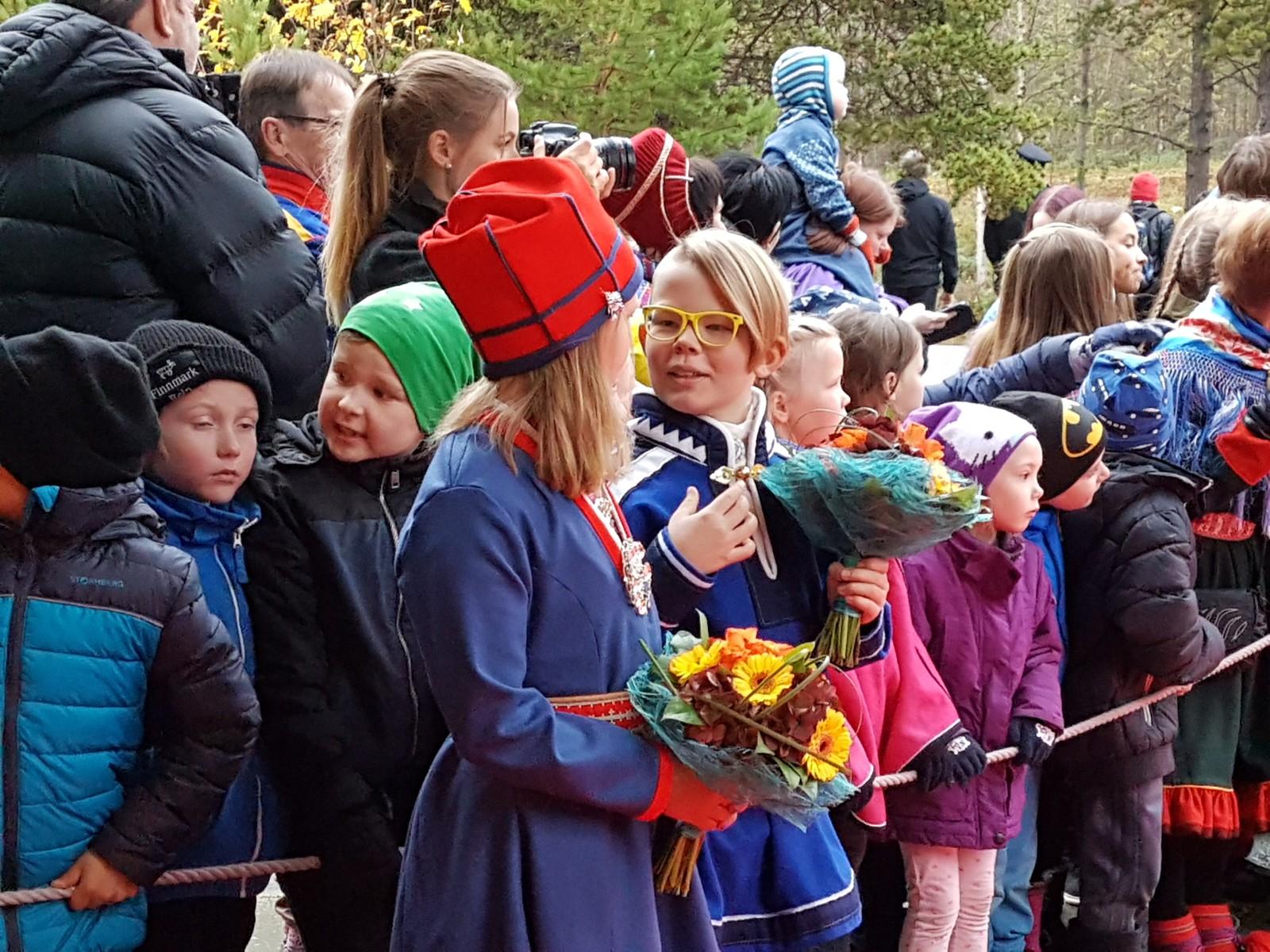 Storm Andre Christensen (10) og Eli Máret Kappfjell Gaup (9) står klare med blomster til Kongen og Kronprinsen.