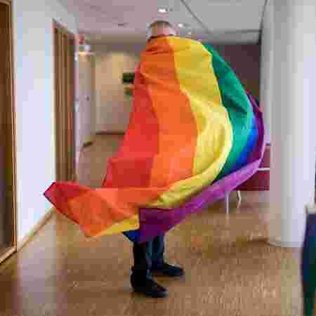 Aasmund har hele kroppen dekket av regnbueflaget