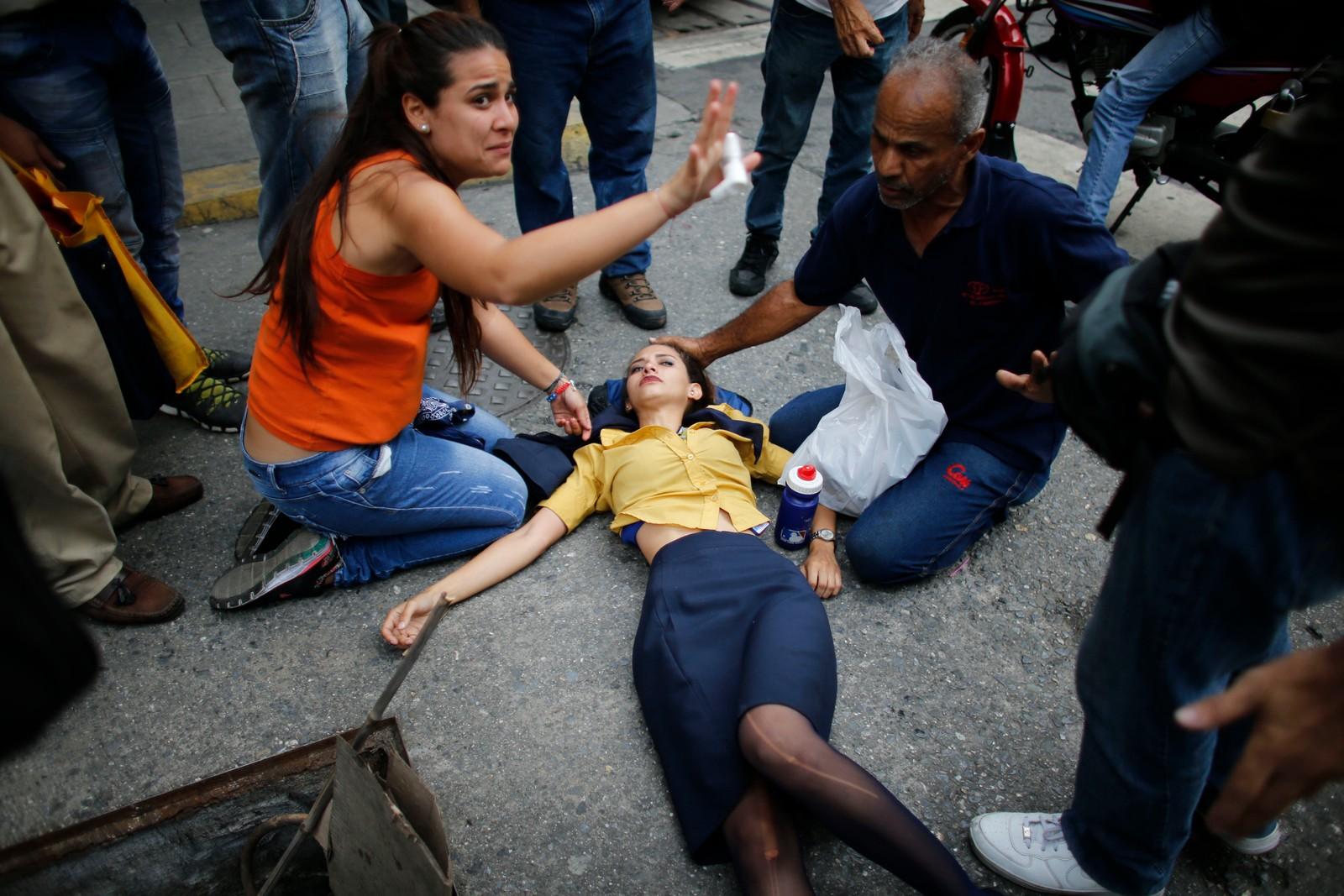 En kvinne får hjelp etter å ha pustet inn tåregass.