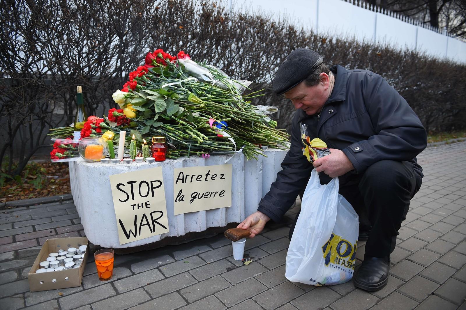 En mann la igjen et stykke brød på en kopp med vodka i utenfor den franske ambassaden i Moskva.