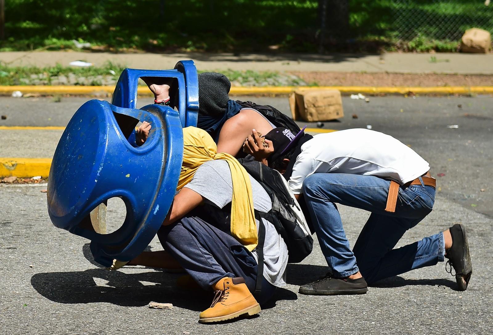 Studenter forsøker å beskytte seg mot tåregass og gummikuler skutt mot dem av opprørspoliti under en demonstrasjon i Caracas i Venezuela. Demonstrantene krever at det skal holdes en folkeavstemning om president Nicolas Maduro skal få fortsette i jobben.