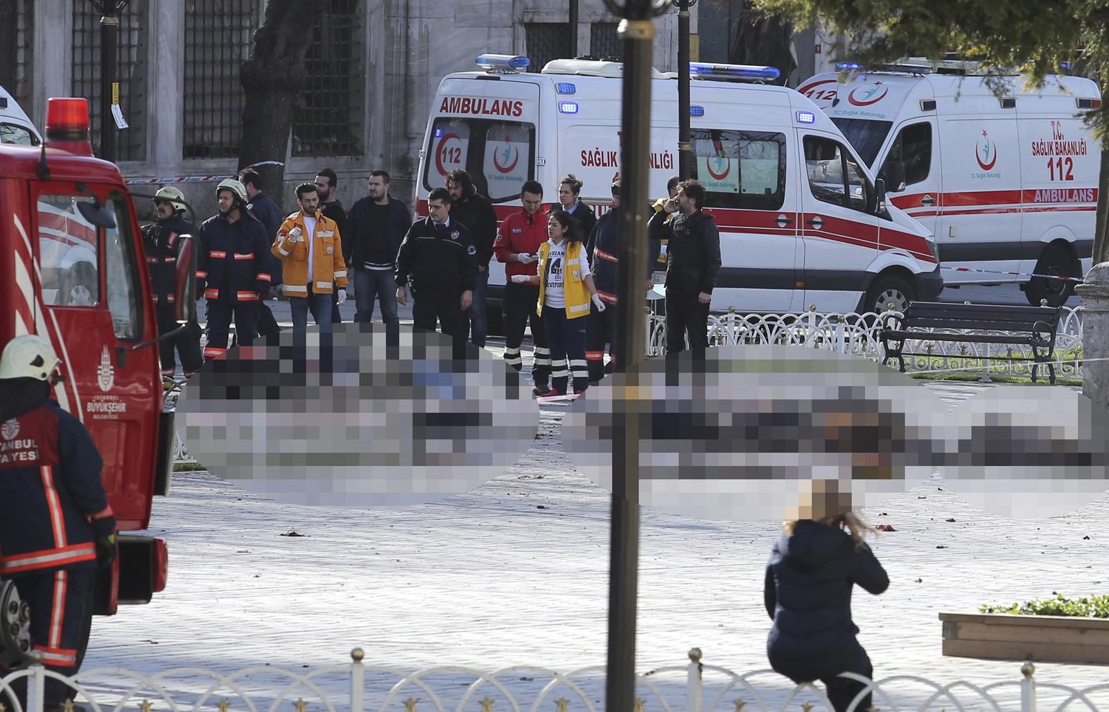 Politiet har sperra av eit stort område og ambulansepersonell tek seg av dei såra etter eksplosjonen.
