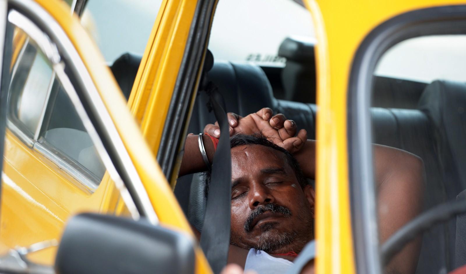 En drosjesjåfør tar seg en blund i bilen i Kolkata i India. Sjåførenes fagforening har oppfordret sjåførene til å holde seg unna veien mellom kl. 11 og 16 når sola steker som verst.