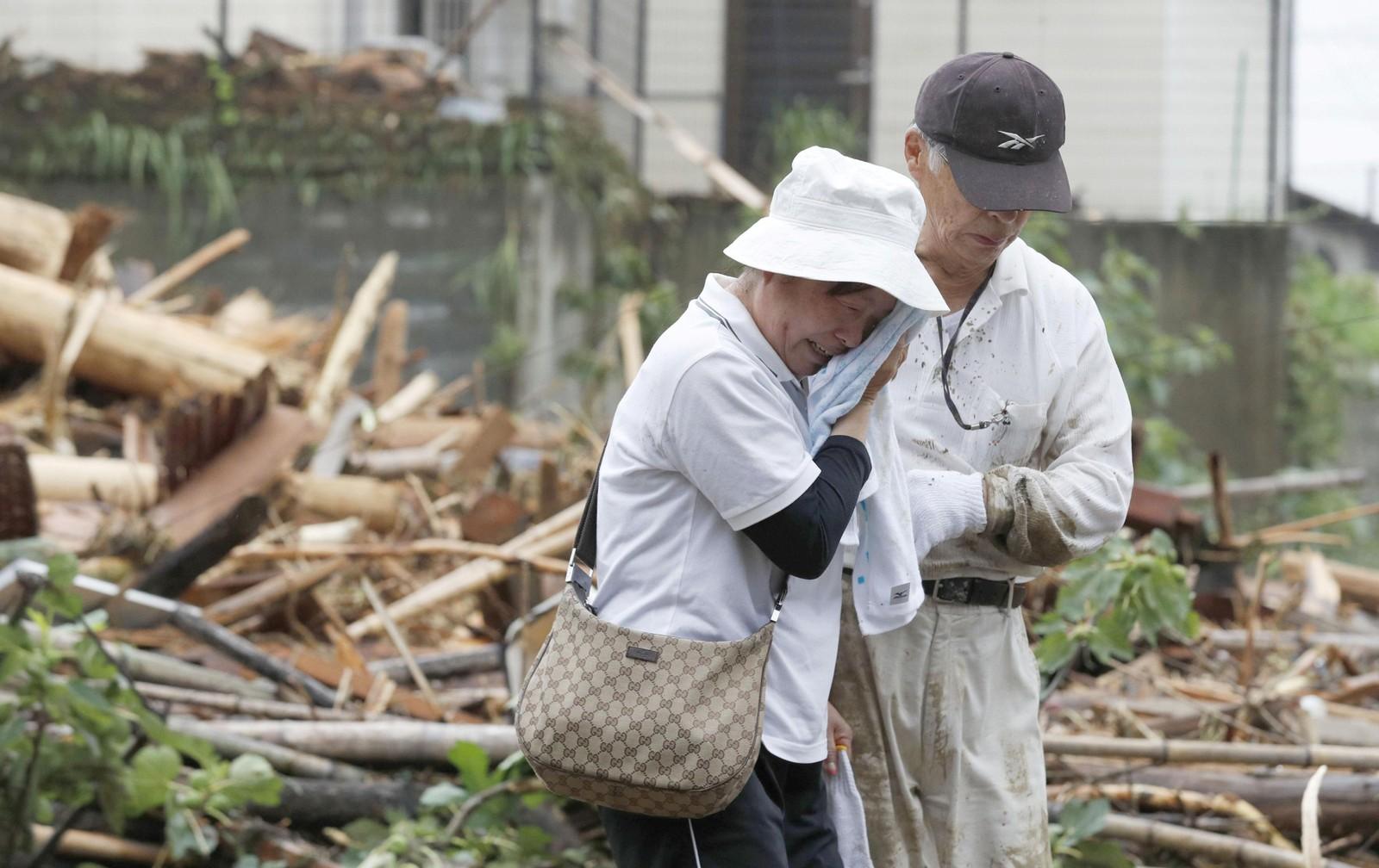 En kvinne gråter over en slektning som er rammet etter det kraftige regnet i Asakura, Japan.