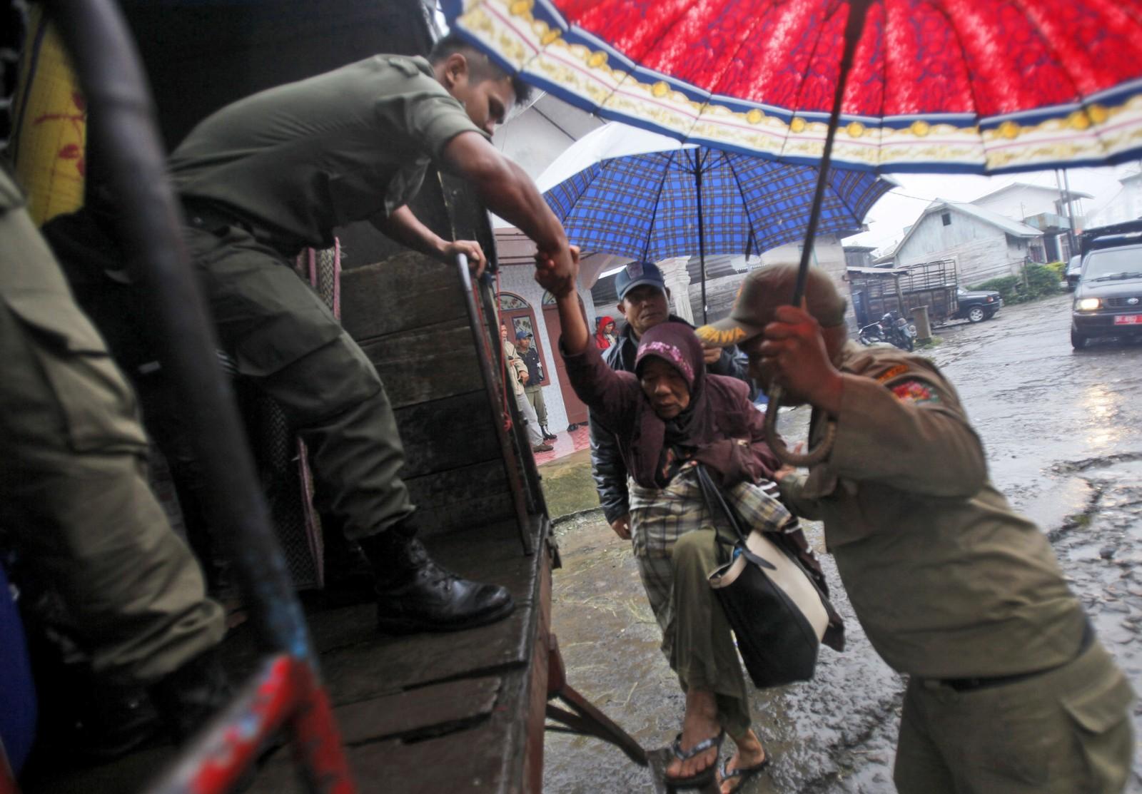 En eldre kvinne blir hjulpet opp på lasteplanet. Flere tusen er evakuert fra dalsidene under Sinabung-vulkanen.