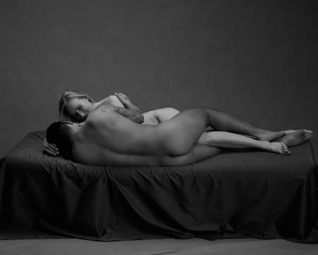 En mann med tatovering og en kvinne med blondt hår ligger på sida på en svart madrass. Han har rumpa mot kamera og holder rundt kvinnen. Hun stryker ham på hodet og smiler.