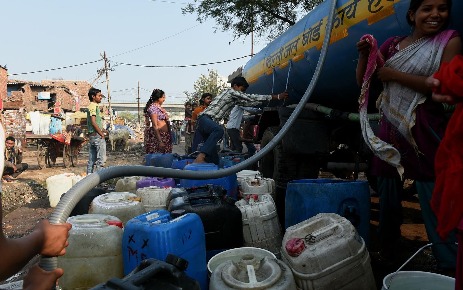 Innbyggere fyller vanntankene sine i en slum i New Delhi.