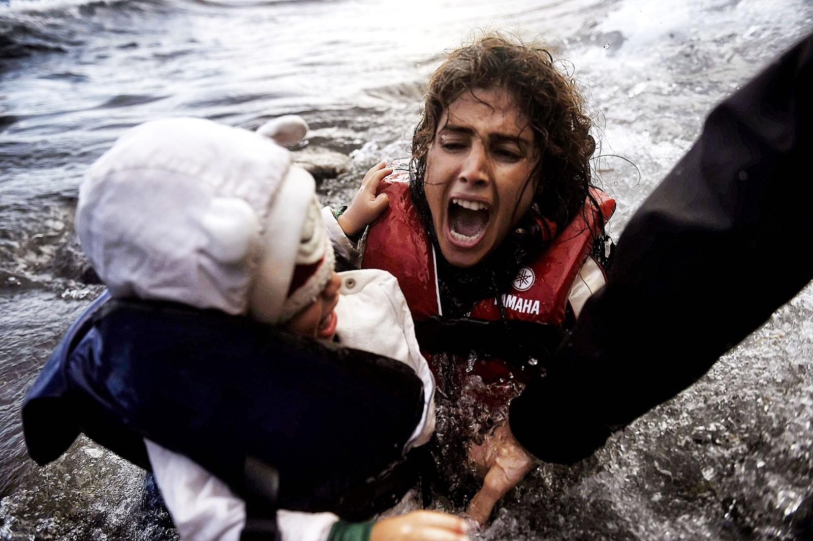 En kvinne og hennes datter faller i vannet i det de hjelpes opp av en gummibåt etter å ha krysset havstrekket mellom Tyrkia og Lesvos 2. oktober 2015.