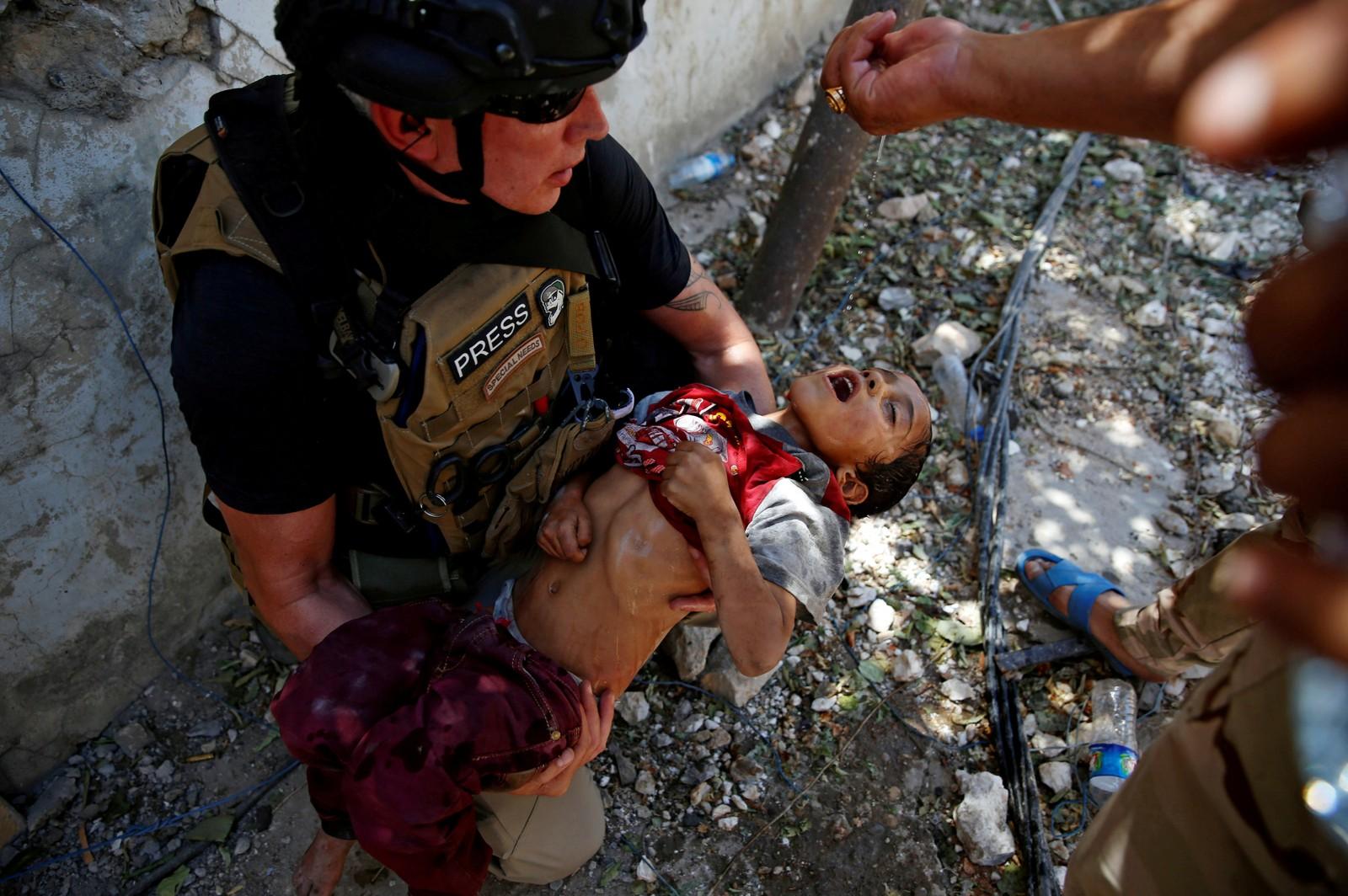 Et barn får i seg noen dyrebare dråper vann etter å ha blitt redda fra kampene i Mosul fra irakiske styrker.