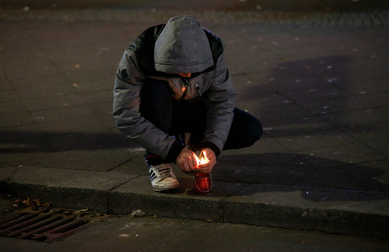 En mann tenner lys for ofrene.
