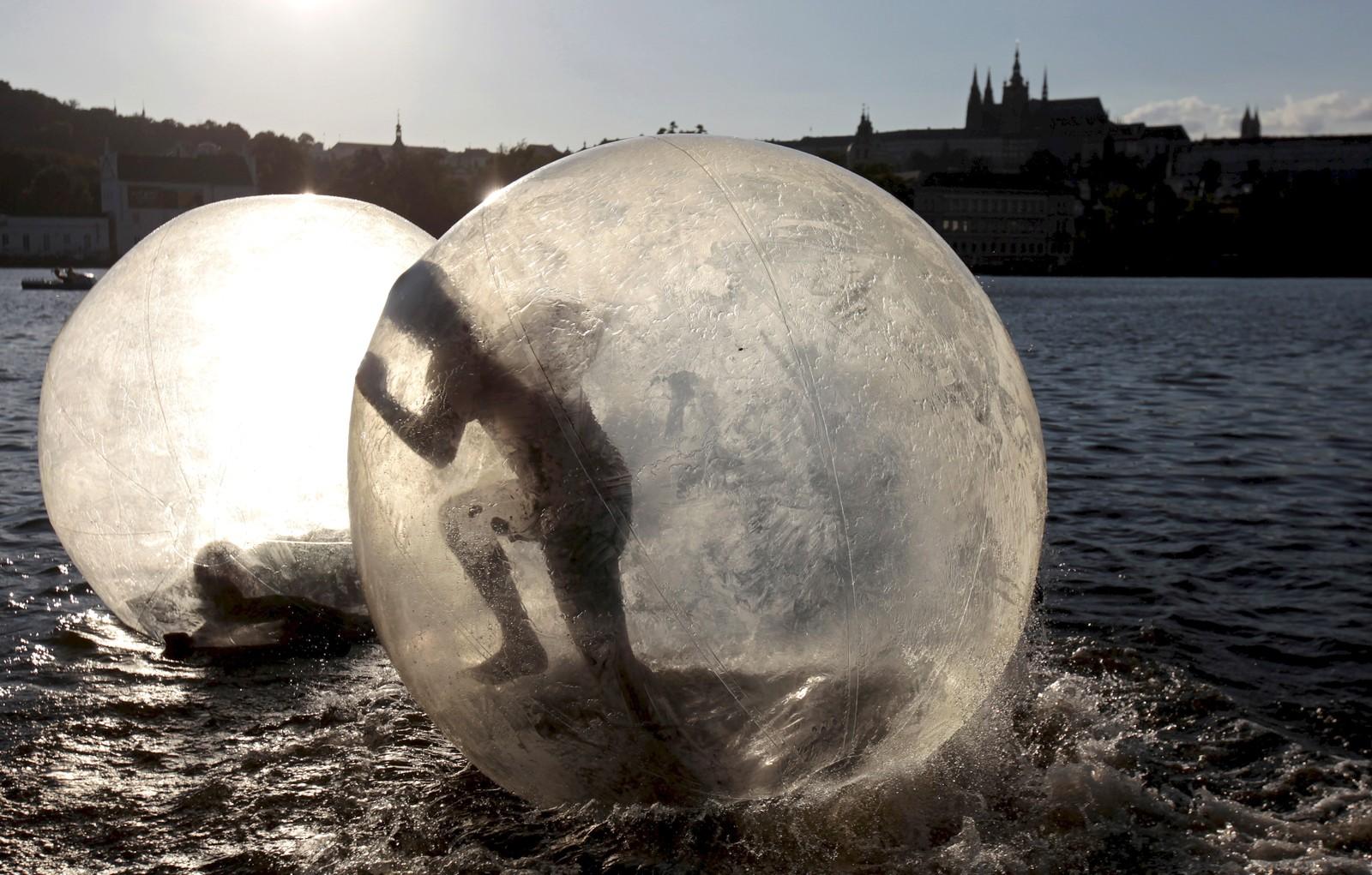Folk leker seg inni gigantiske plastballer i sommervarmen på Vltava-elven i Praha. Det har vært varmt og godt i den tsjekkiske hovedstaden denne uken, med temperaturer opp mot 34 grader.
