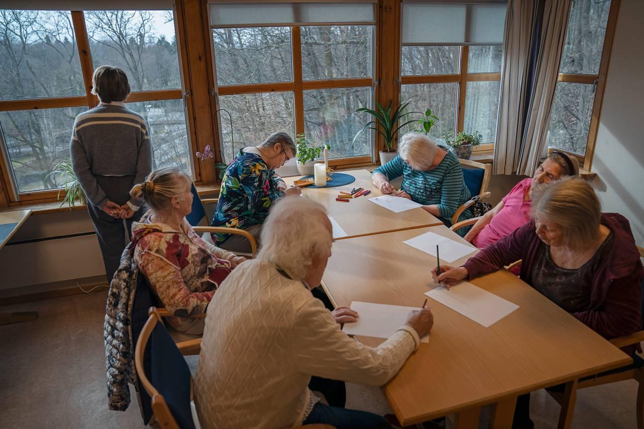 Syv beboere sitter sammen og tegner rundt bordet i oppholdsrommet. Den ene har sovnet, en annen stirrer rolig ut av vinduene med hendene knyttet bak ryggen.