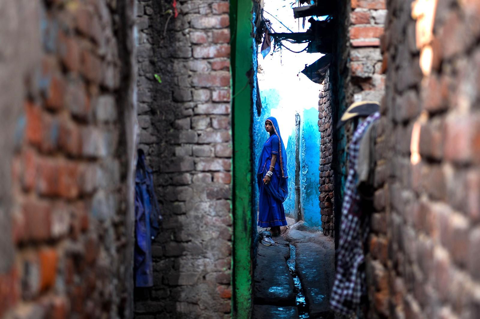 """En indisk kvinne står i et smug i Kathpuli-kolonien i New Delhi i India. Kathpuli er et slumområde. På hindi betyr navnet """"tredukke"""". Innbyggerne er for det meste illusjonister, akrobater, dansere og musikere."""