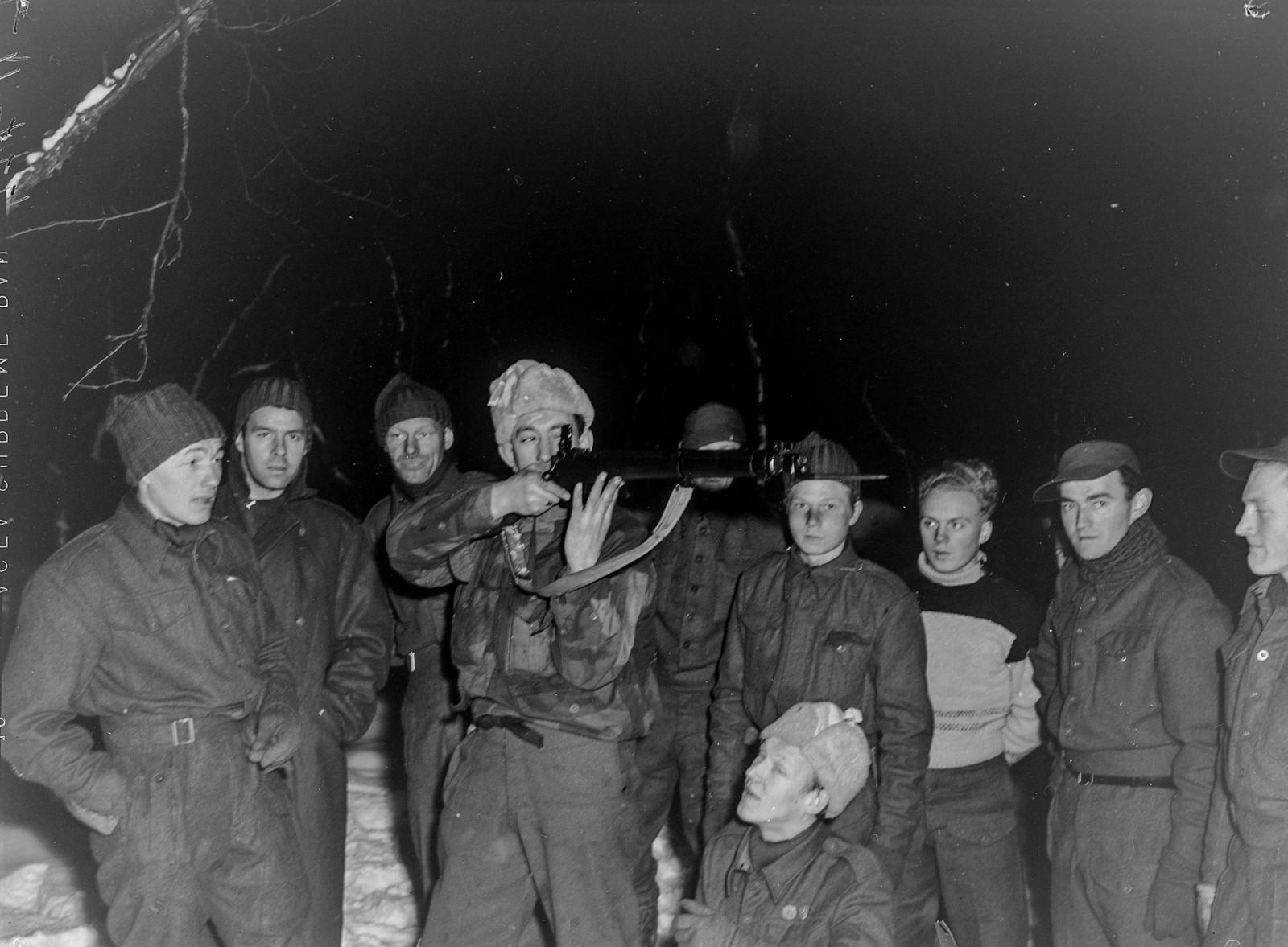 Original bildetekst: Allerede de første dagene etter befrielsen av Kirkenes meldte omlag 1.500 nordmenn seg som frivillige til de norske styrkene. Under ledelse av norske offiserer tok de straks opp trening og vaktarbeide i de befriede områder. En ser her skyteøvelser i den arktiske vinternatten