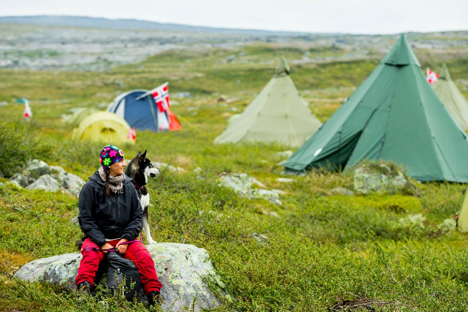 En kvinne og hennes hund blant telt før fjerde og siste etappe i sykkelrittet Arctic Race of Norway søndag.