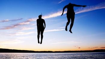 To personer bader og hopper uti vannet