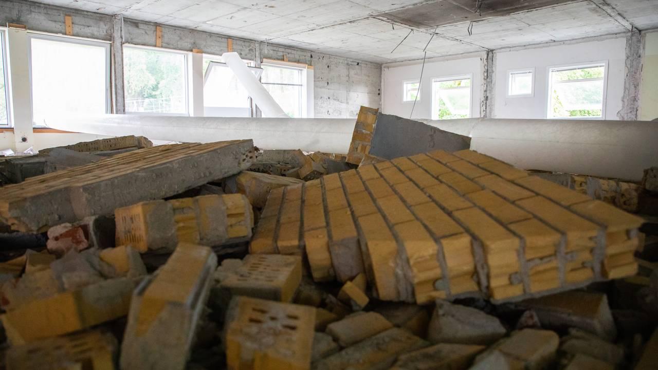 På gulvet ligger det flere flak av murstein etter at veggen har blitt revet. Det er særlig fokus på et ganske stort flak helt fremme i bildet. Bare betongen står igjen av tak og vegger. Et rør for ventilasjon er lagt gjennom rommet og ut av vinduet.