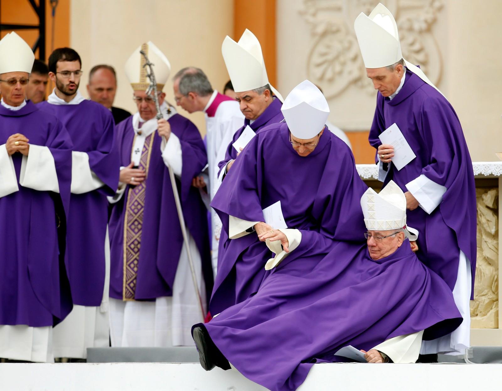Opp igjen! Biskop Claudio Stagni får hjelp til å komme seg på beina under en messe i Capri i Italia.