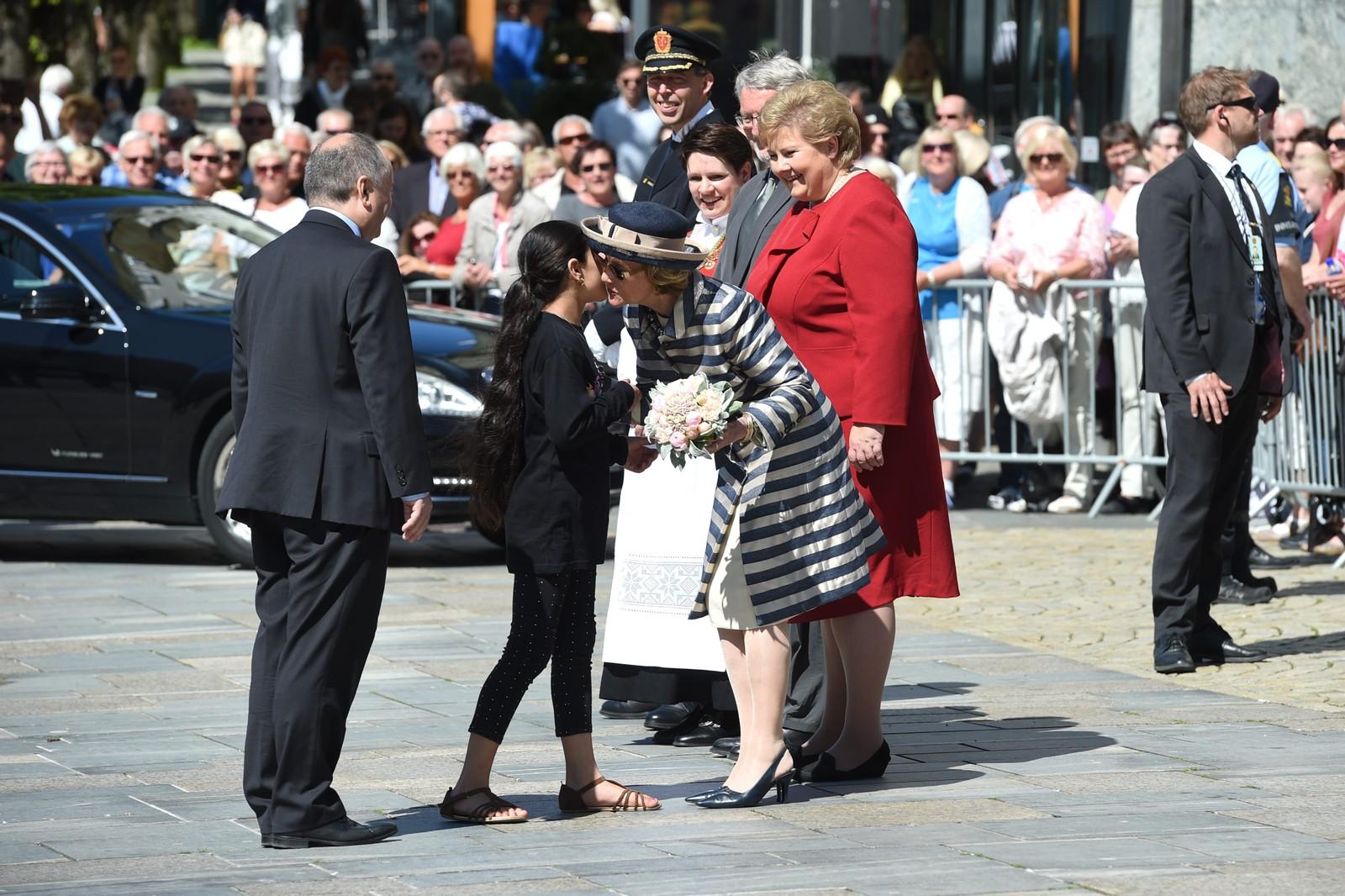 Sali (11) gir blomster til Dronning Sonja. Statsminister Erna Solberg, bergensordfører Marte Mjøs Persen og politimester Kaare Songstad følger med.