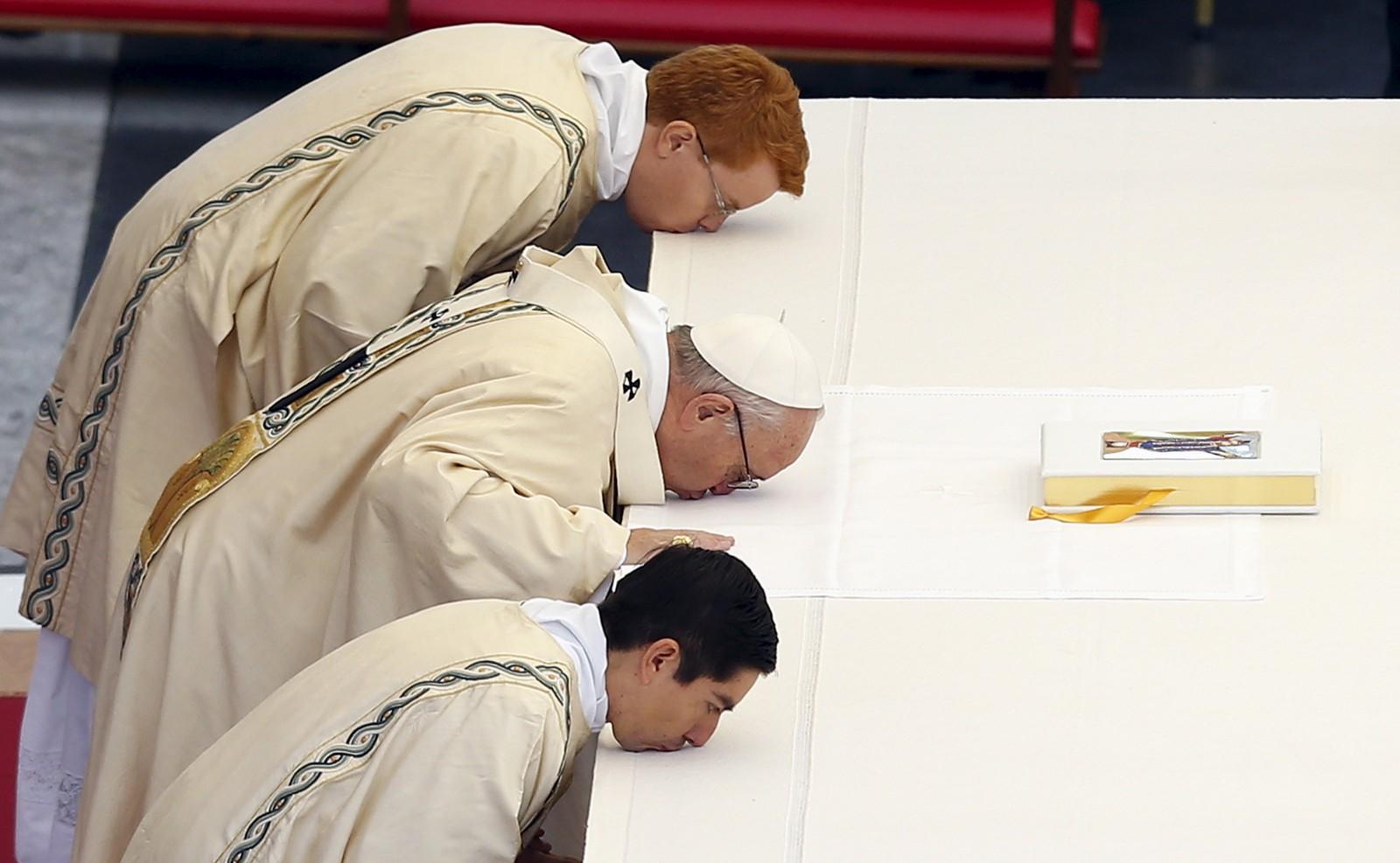 Pave Frans (i midten) kysser alteret under en messe som markerer åpningen av jubileet for katolisismens hellige år i Vatikanet.