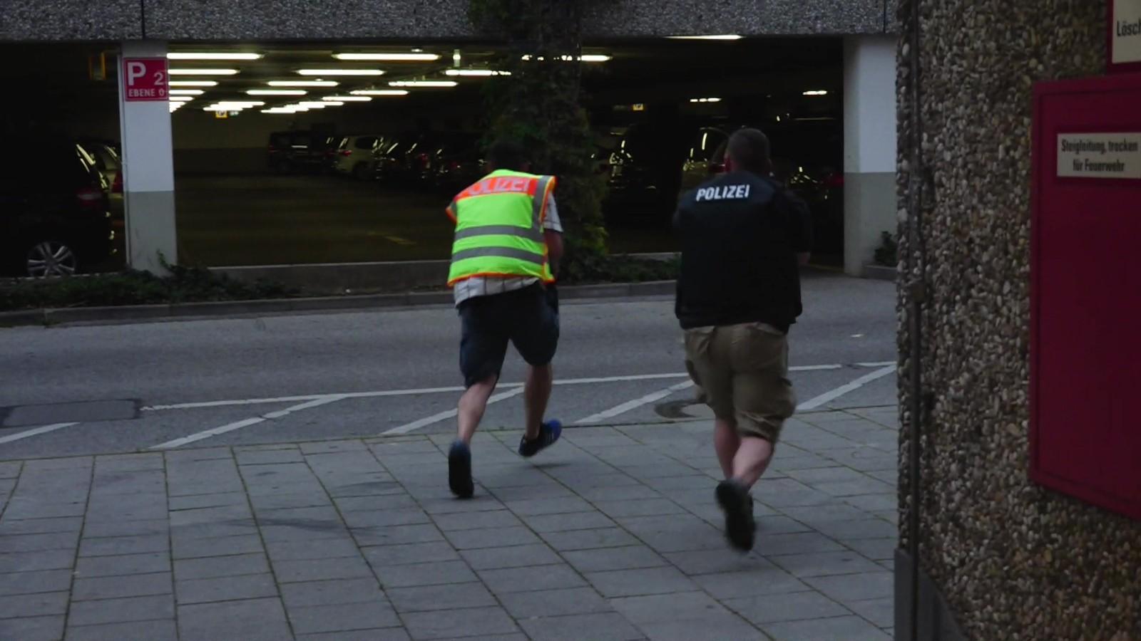 SPRINGER MOT KJØPESENTERET: Bilde fra video som viser sivilt politi som springer mot parkeringshuset ved kjøpesenteret der skytingen begynte fredag kveld.