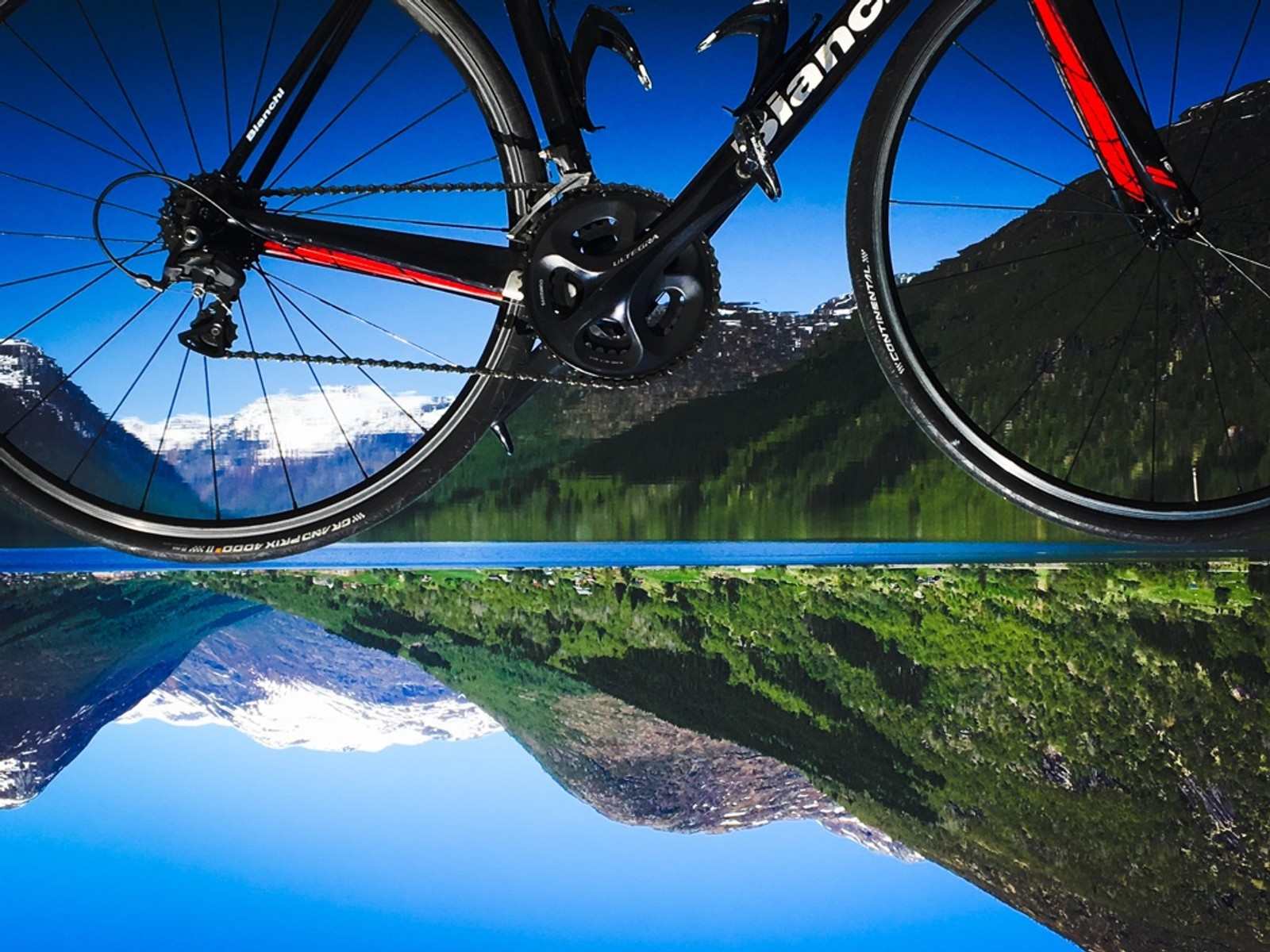 Ny og moderne sykkel, med snødekte fjelltoppar som speglar seg i Jølstravatnet.
