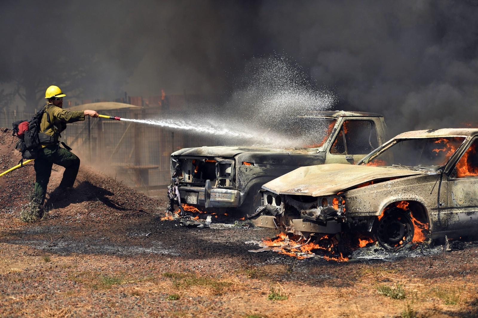 Brannmannskap slukker brennende biler i Lower lake søndag.