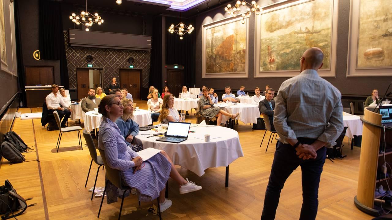 I en stor sal på Grand Hotel i Bergen sitter et titalls ansatte fra næringslivet i Bergen samlet ved runde bord. Det hanger malerier på veggene og lysekroner fra taket. Vi ser ryggen til Svein Egil Dagsland, som holder foredrag.