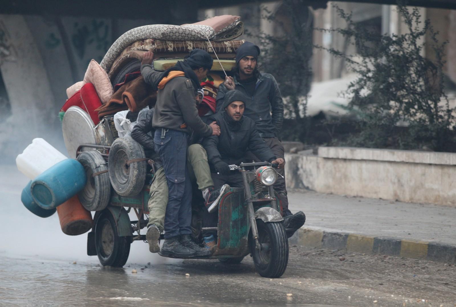 Menn på en fullastet moped, kjører i Aleppos gater.