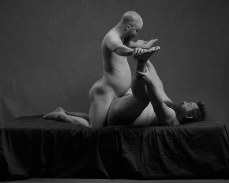 En naken skjeggete mann ligger på ryggen med bena ut til hver side mens en annen naken mann med skjegg står på kne mellom bena hans og holder på fotsålene til mannen som ligger på ryggen.