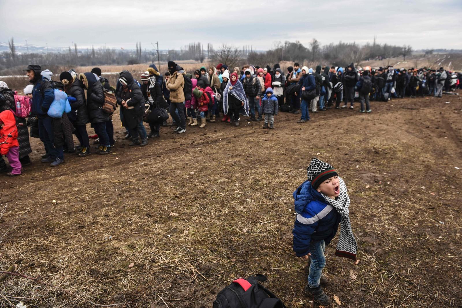 En liten gutt står og roper ved siden av den endeløse lange køen på grensen mellom Makedonia og Serbia.