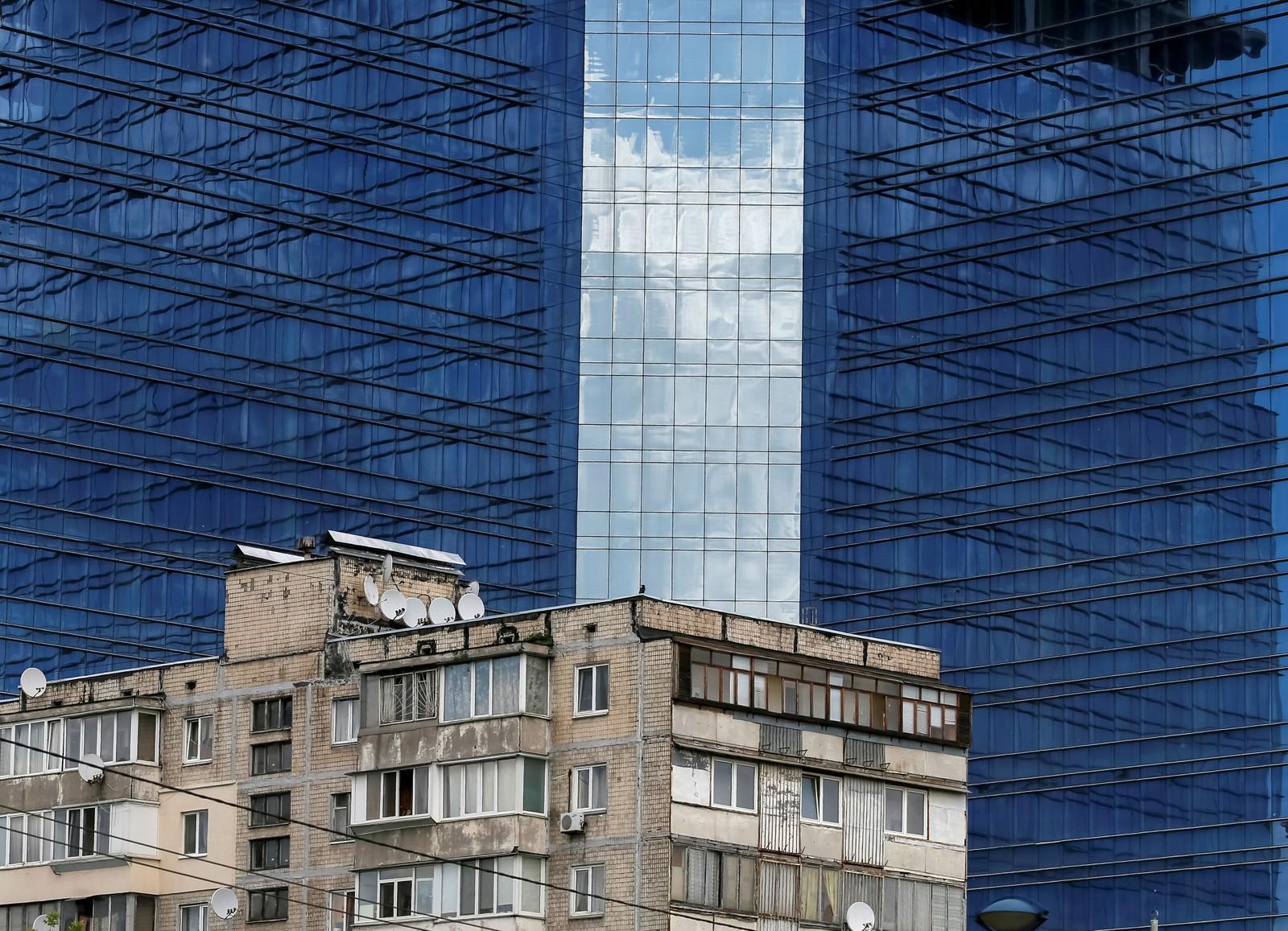 Gammelt og nytt i Kiev i Ukraina. En gammel leilighetsbygning og et handelssenter som er i ferd med å bygges ferdig.