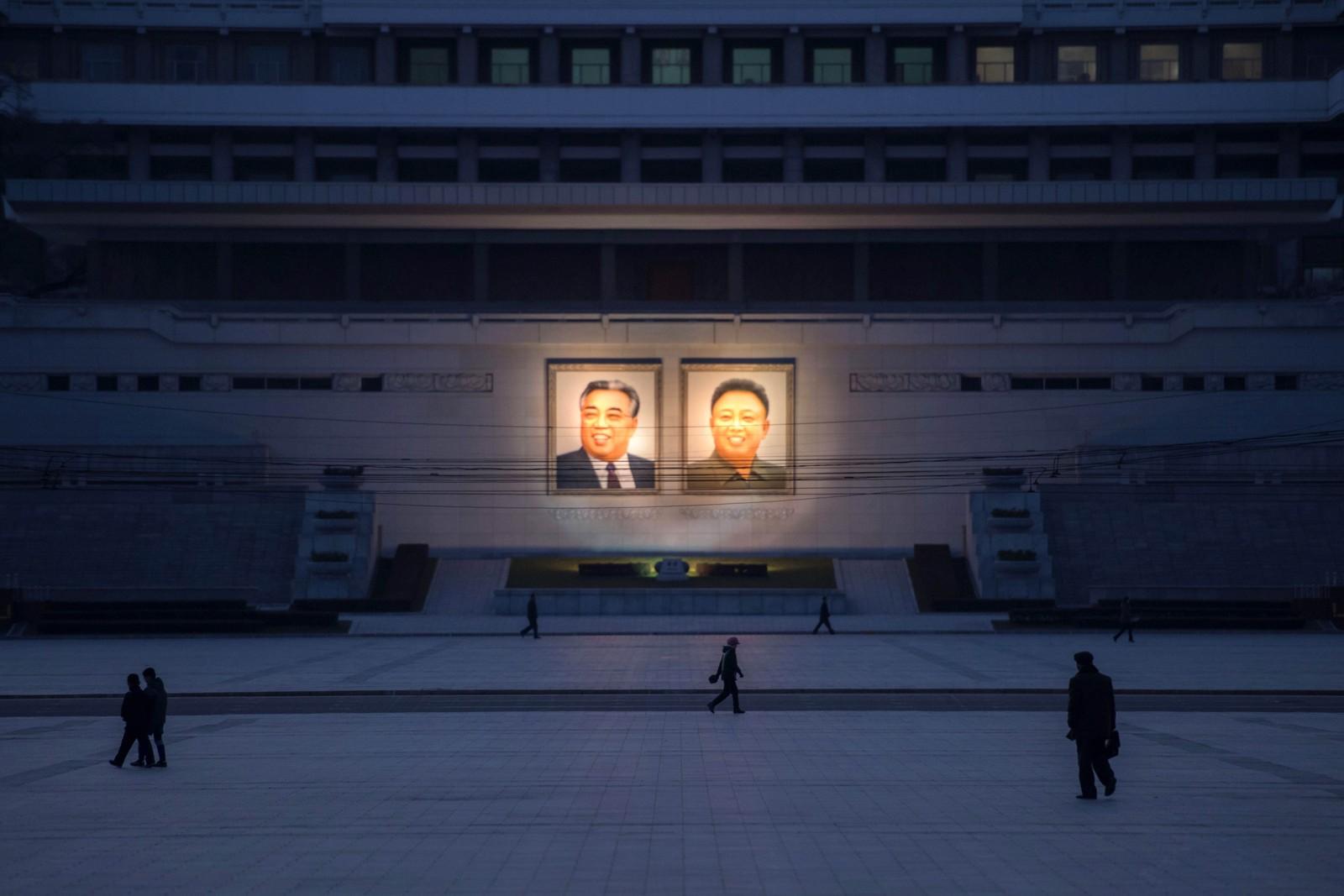 Fotgjengere går forbi portretter av Kim Il-sung Kim Jon-il i Pyongyang i Nord-Korea.