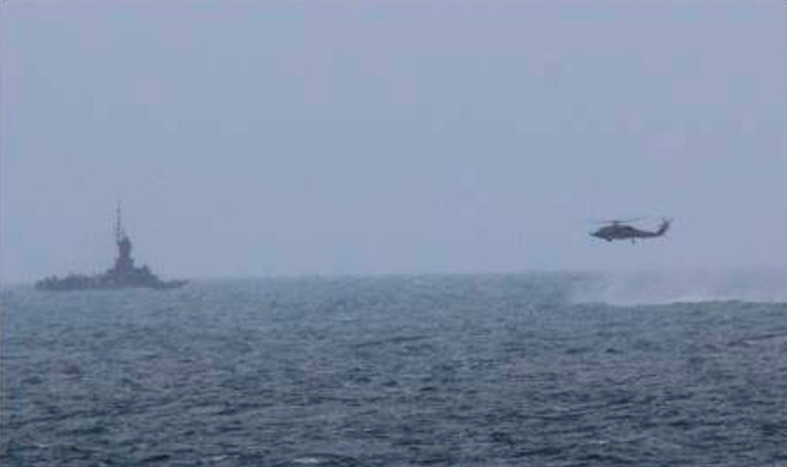 Et helikopter tilknyttet det amerikanske marinefartøyet USS Sampson flyr mot et indonesisk patruljefartøy under søket etter vrakdeler i Javasjøen onsdag.