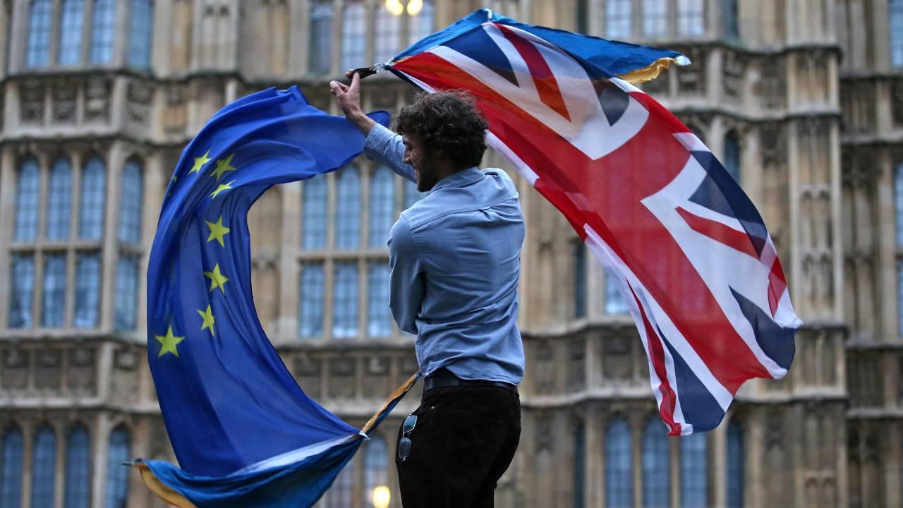 Mann med EU-flagg og britisk flagg