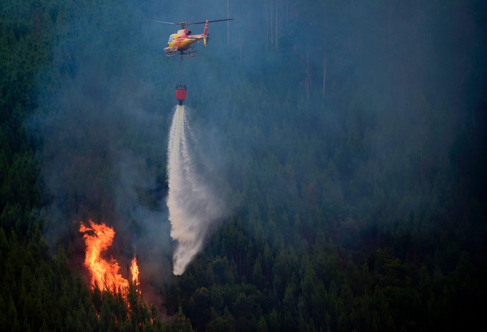 Helikopter flyr inn vann til brannområdene i Carvalho 19. juni.