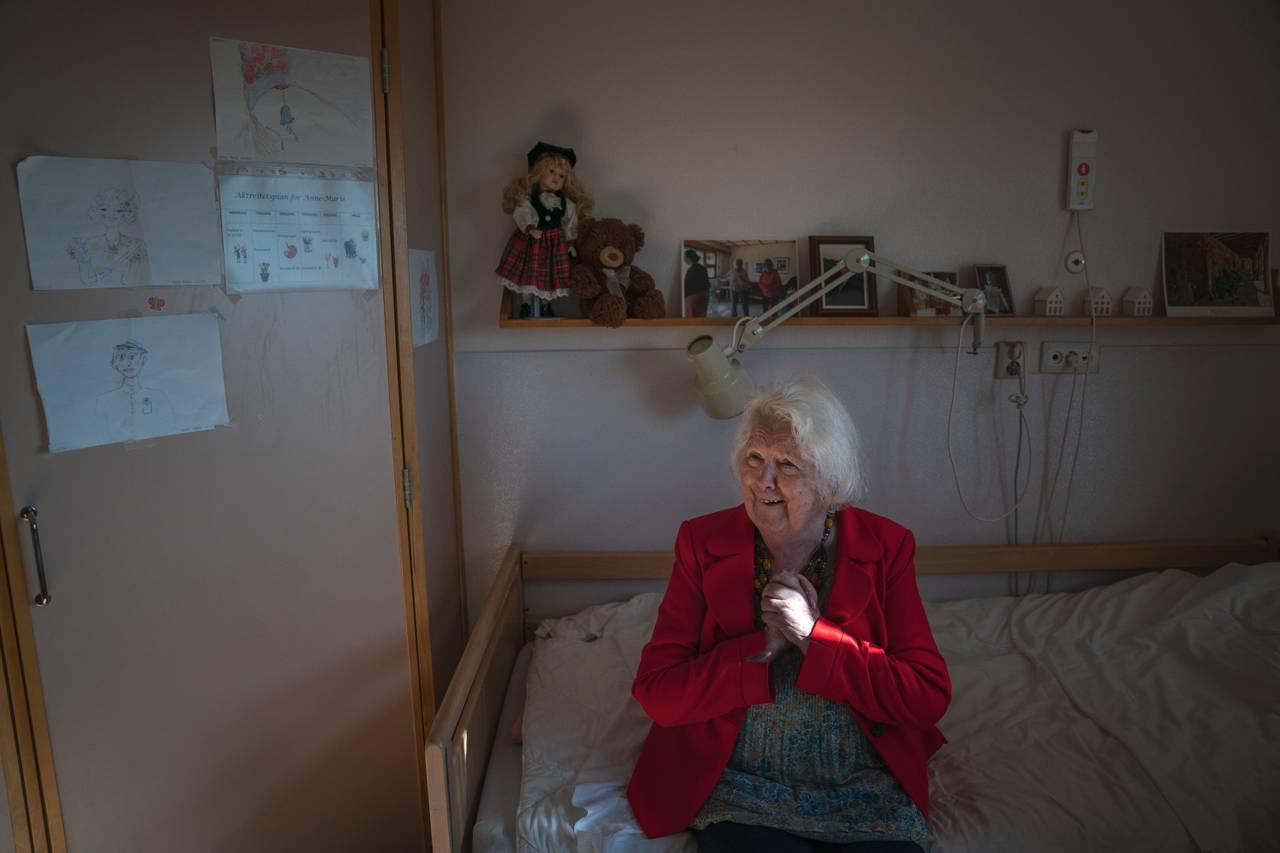 Kvinne i rød jakke sitter i seng og knytter hendene mens hun smiler stort. På veggen bak ser man en hylle med en rekke fotografier på en, en dukke, en teddybjørn og noen barnelignende tegninger på veggen ved siden av.